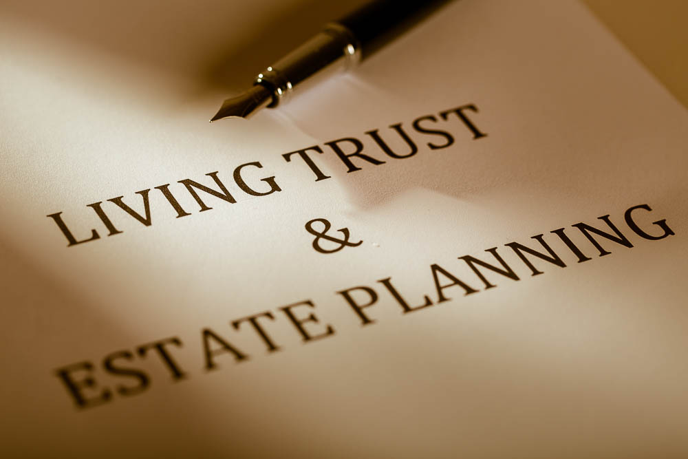 "Fountain Pen Lying on the ""Living Trust and Estate Planning"" - Close Up"